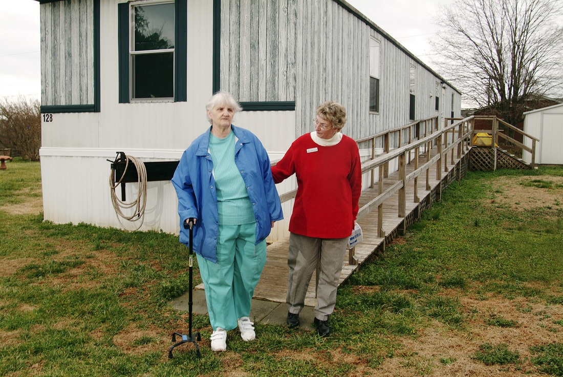 A volunteer holds the arm of an elderly women with a cane in front of the elderly women's house.
