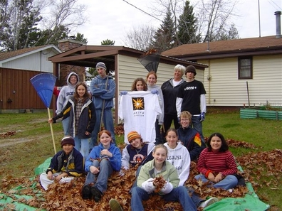 a group of children standing around and  sitting in a big pile of leaves  they raked from and elderly persons yard.